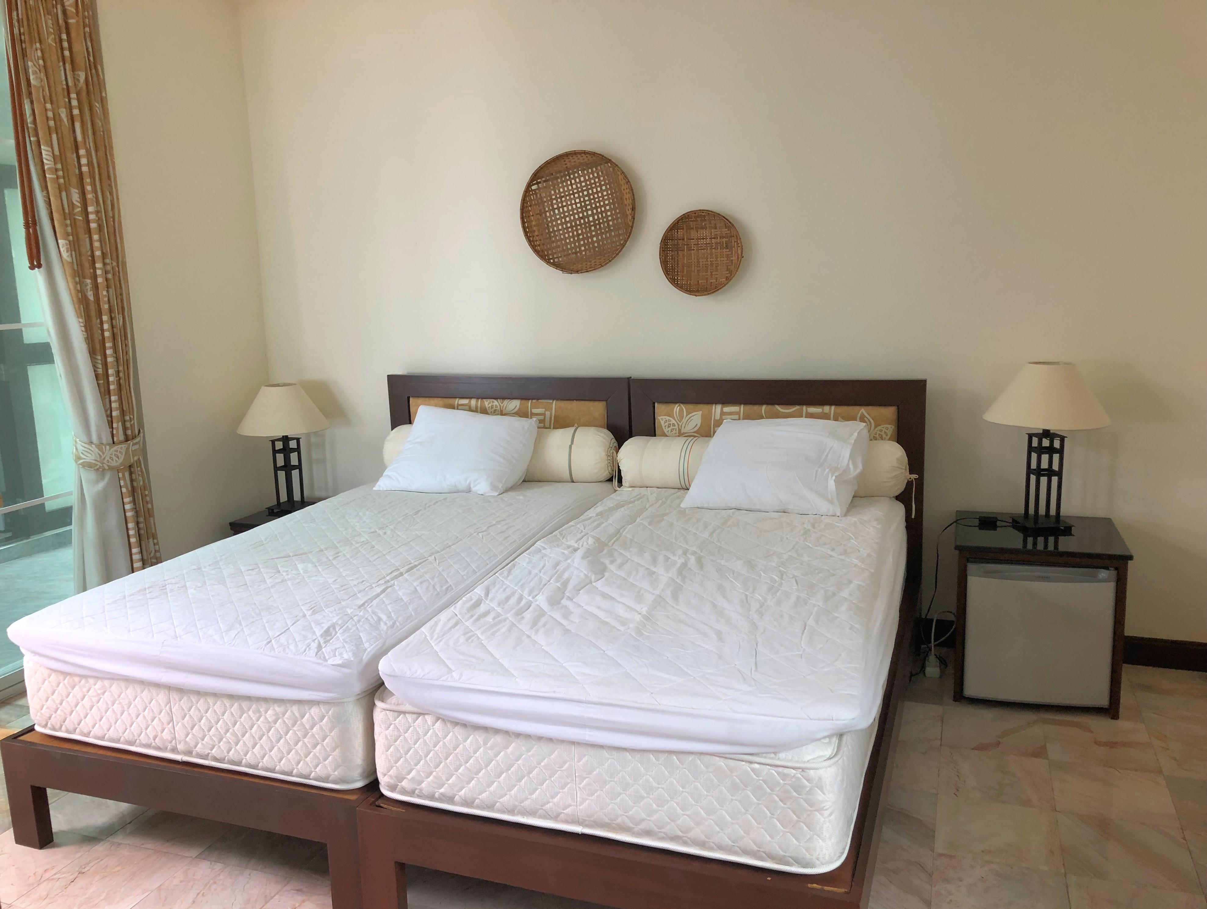 Gästsovrum med samma typ av sängar som master bedroom. Nattduksbord och en liten kyl.